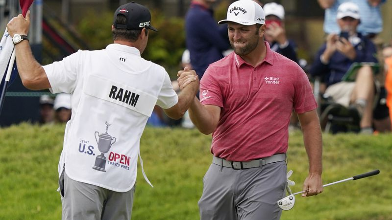 Jon Rahm, of Spain, celebrates with his caddy after making his birdie putt on the 18th green...