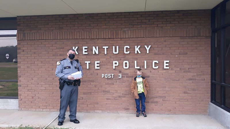 Ayden poses with an officer in front of KSP post 3.
