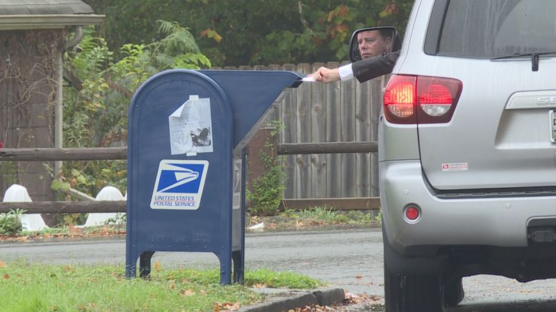 Person drops mail in USPS drop box