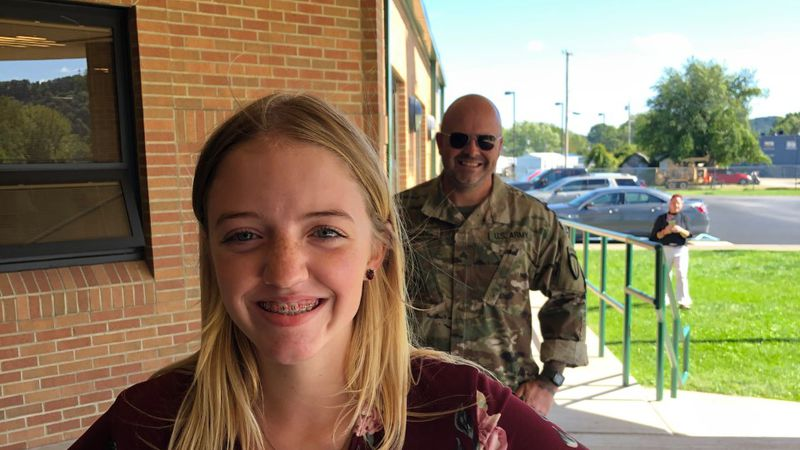 U.S. Army soldier Clifford Hankins stands behind his daughter Harley to surprise her  at school...