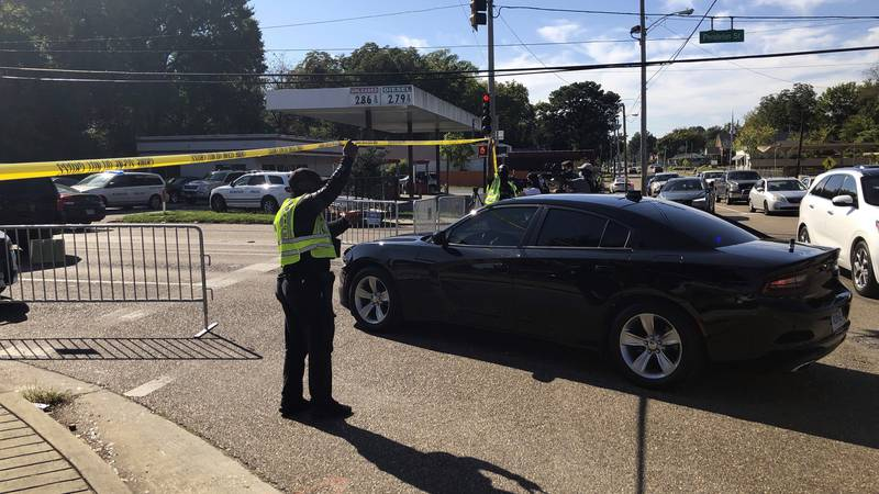 Officers allow a police vehicle to pass under yellow crime scene tape on a street in front of...