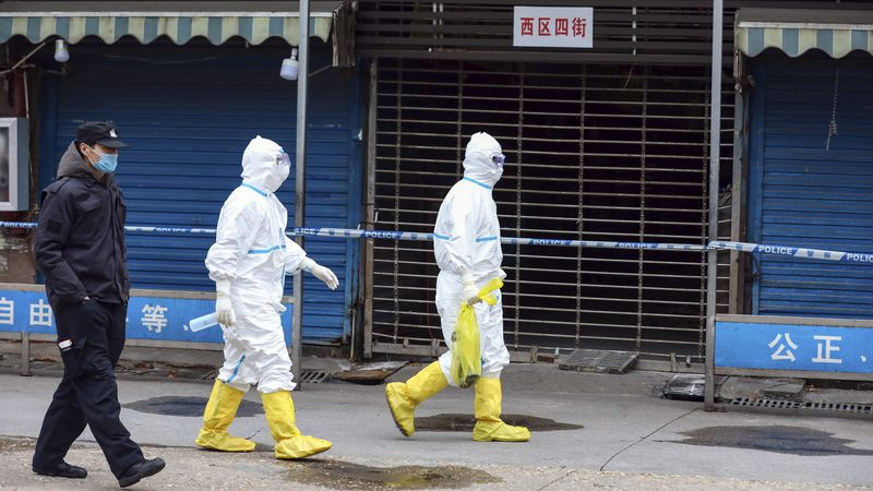 In this Jan. 27, 2020, file photo, workers in protective gear carry a bag containing a giant...