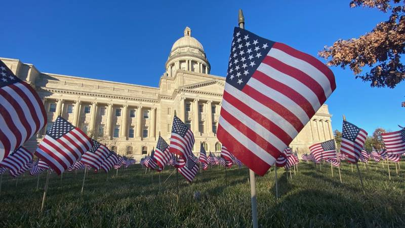Outside the Kentucky Capitol, 5,005 American flags blow in the wind. Each one signifies a...
