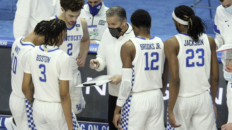 Kentucky head coach John Calipari, center, draws up a play during the first half of an NCAA...