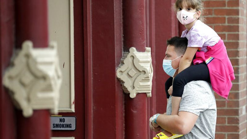 A man and a girl wear masks as they stop to hear a band outside a music venue Monday, June 29,...