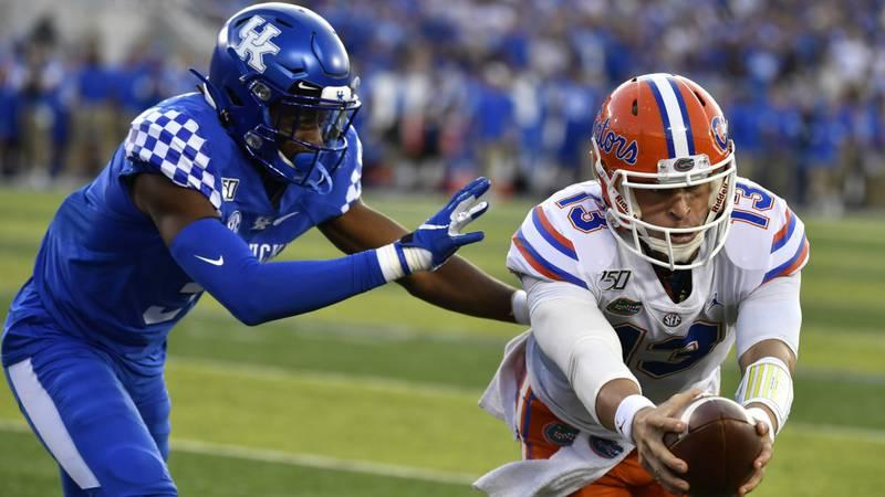 Florida quarterback Feleipe Franks (13) reaches for extra yards ahead of Kentucky safety Jordan...