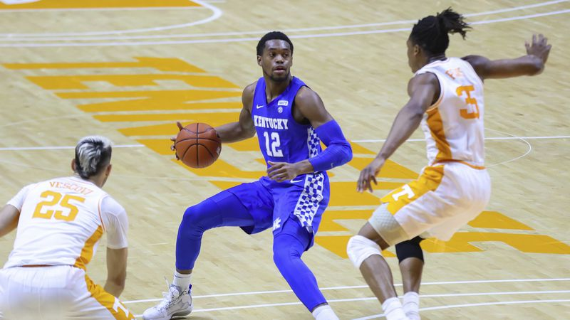 Kentucky's Keion Brooks Jr. (12) brings the ball up court against Tennessee's Yves Pons (35)...