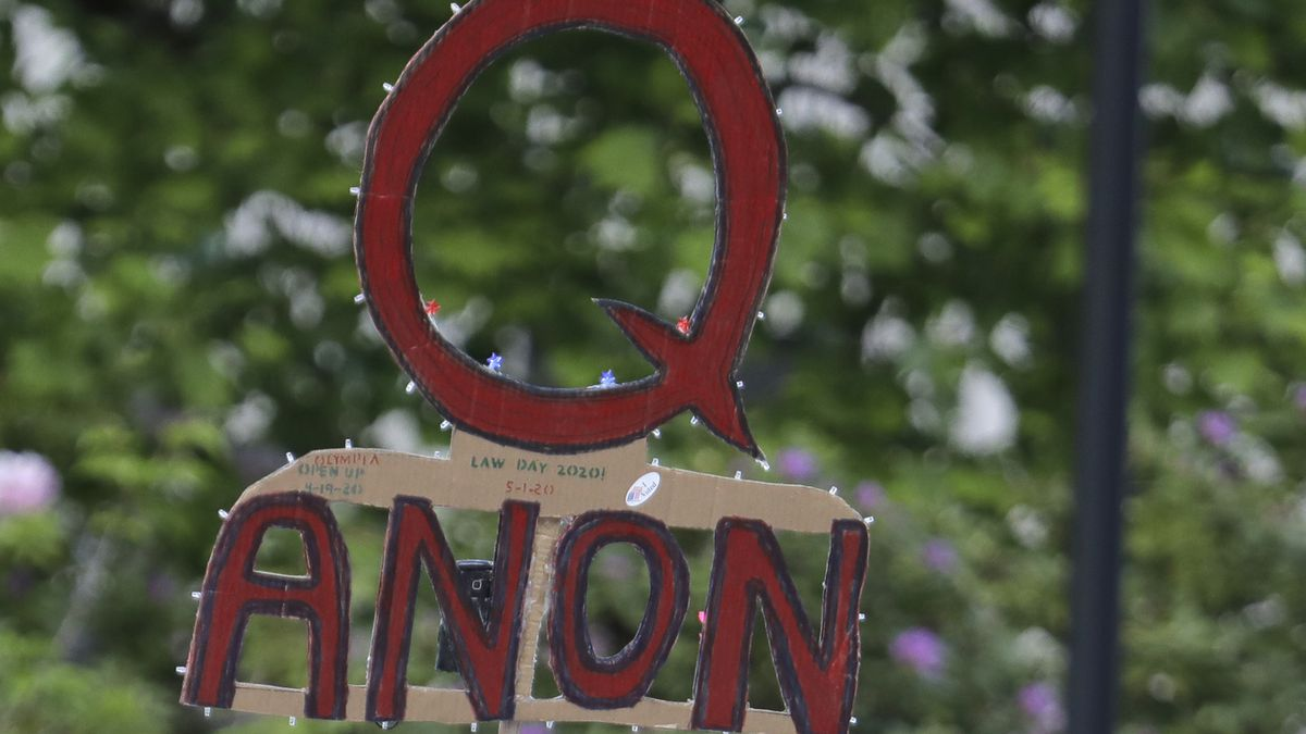 FILE - In this May 14, 2020 file photo, a person carries a sign supporting QAnon at a protest rally in Olympia, Wash.