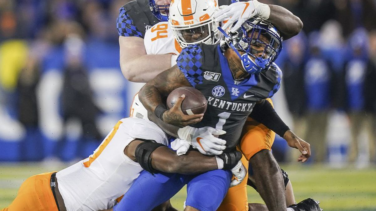 Kentucky quarterback Lynn Bowden Jr. (1) is tackled by Tennessee linebacker Quavaris Crouch (27) and defensive lineman Matthew Butler (94) during the first half of an NCAA college football game, Saturday, Nov. 9, 2019, in Lexington, Ky.