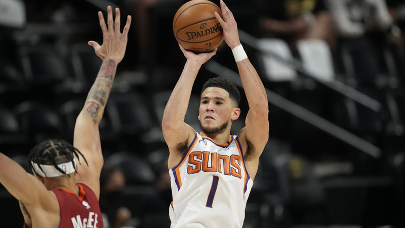 Phoenix Suns guard Devin Booker, right, shoots over Denver Nuggets center JaVale McGee in the...