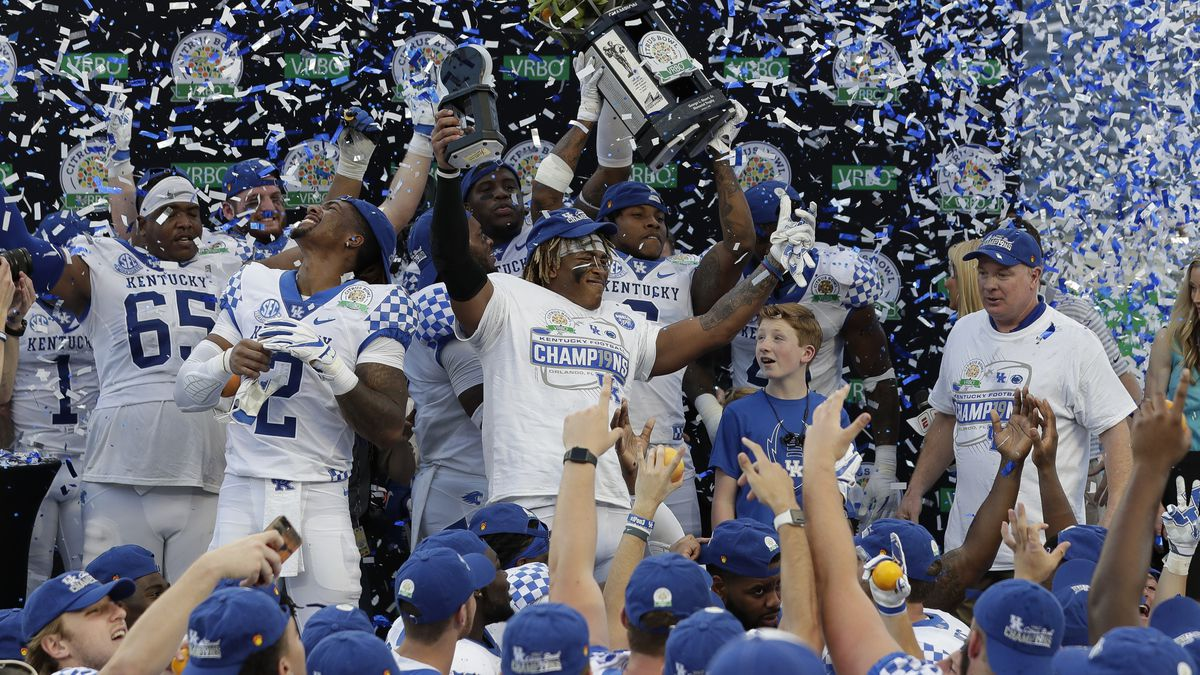 Kentucky players and coach Mark Stoops, right, celebrate after receive the championship trophy...