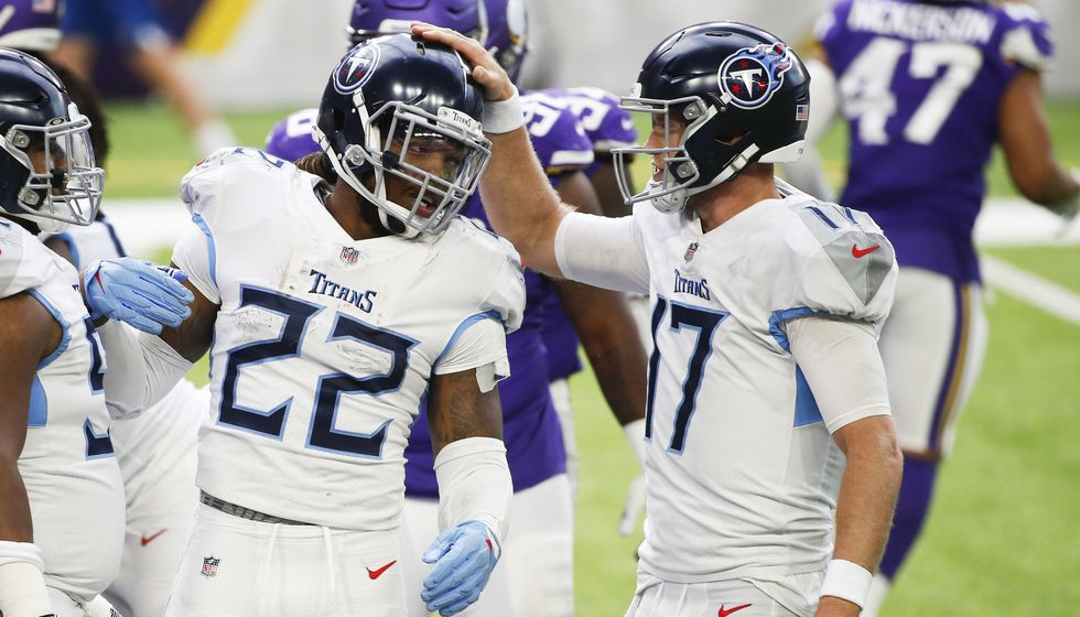 Tennessee Titans running back Derrick Henry (22) celebrates with teammate Ryan Tannehill, right, after scoring on a 1-yard touchdown run during the second half of an NFL football game against the Minnesota Vikings, Sunday, Sept. 27, 2020, in Minneapolis. A coronavirus outbreak shut down team facilities and forced the schedule to be rearranged.