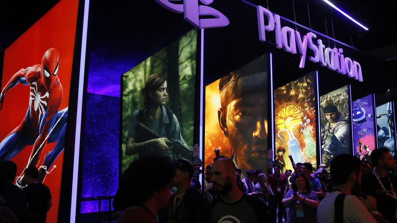 In this June 14, 2018, file people stand online next to the PlayStation booth at the 24th...