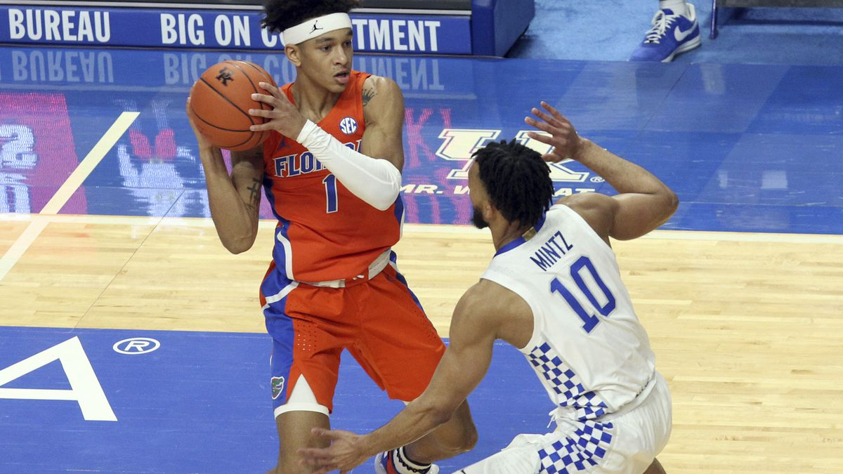 Florida's Tre Mann, left, looks for an opening on Kentucky's Davion Mintz (10) during the first...