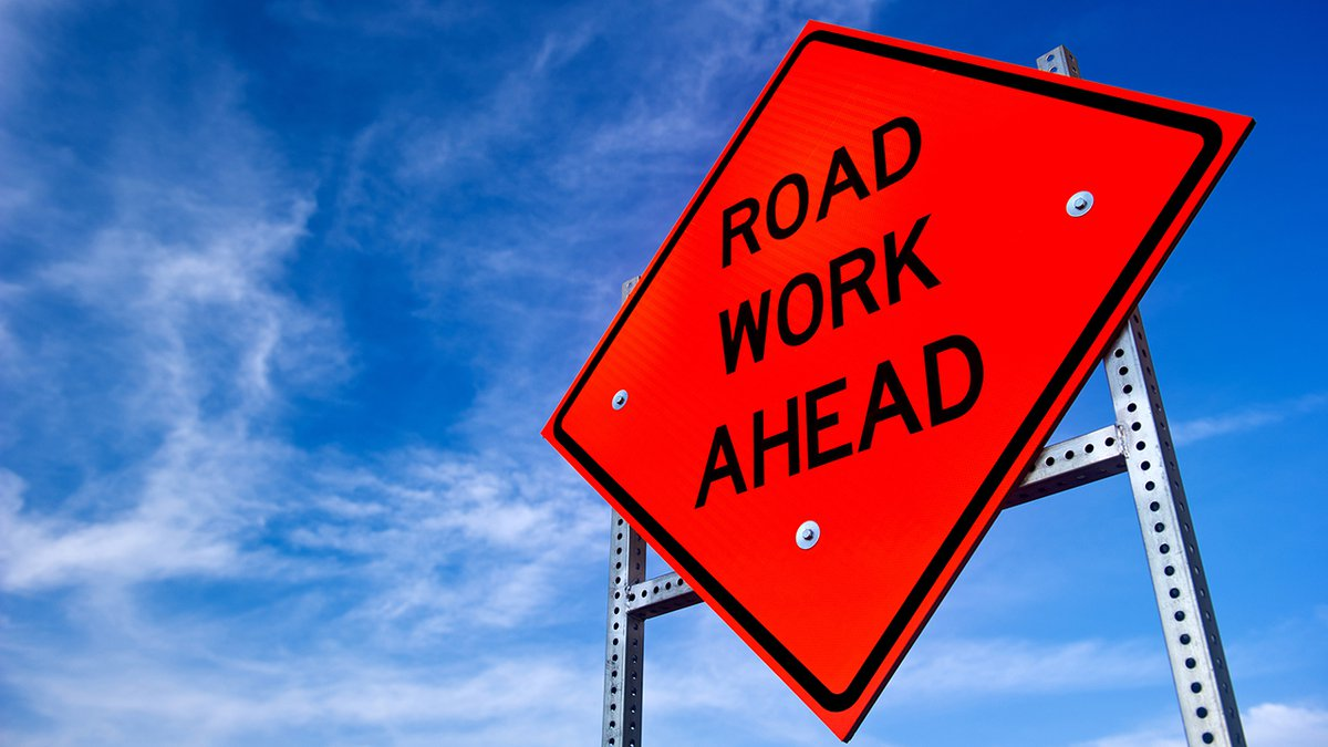 Image of a bright orange road work ahead sign against a blue sky with light clouds