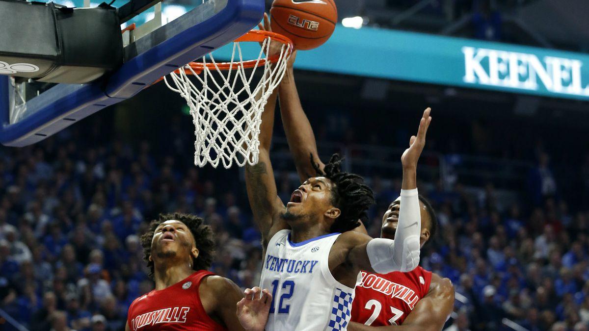 Kentucky's Keion Brooks Jr. (12) shoots between Louisville's Dwayne Sutton (24) and Steven...