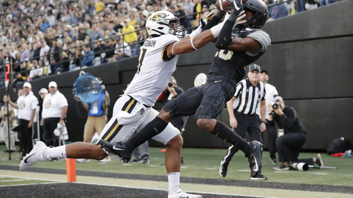 Vanderbilt defensive back Allan George, right, intercepts a pass intended for Missouri tight end Albert Okwuegbunam, left, in the end zone during the second half of an NCAA college football game Saturday,