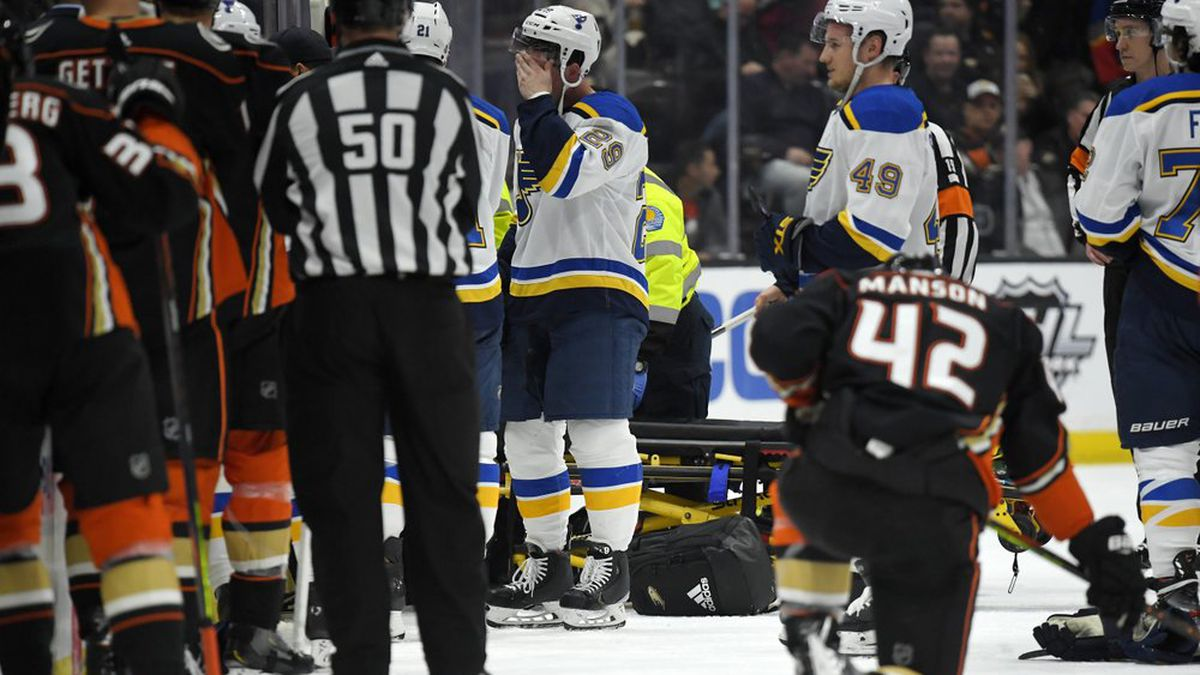 St. Louis Blues defenseman Vince Dunn, left, of center wipes his faces as Anaheim Ducks defenseman Josh Manson kneels on the ice while blues defenseman Jay Bouwmeester, who suffered a medical emergency, is worked on by medical personnel during the first period of an NHL hockey game Tuesday, Feb. 11, 2020, in Anaheim, Calif.