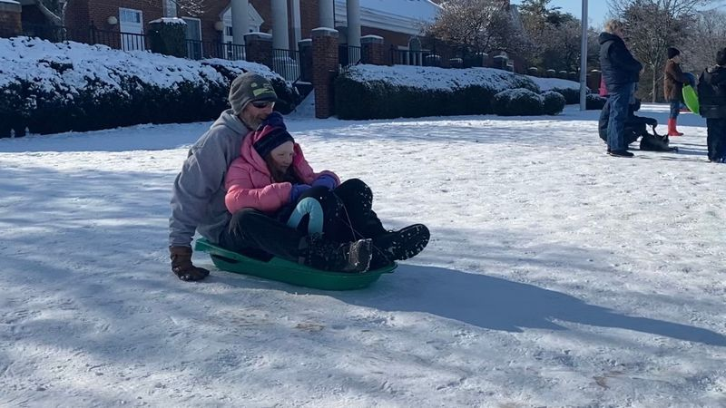 A father and his daughter sled down the hill at the Old Shriners Hospital in Lexington.