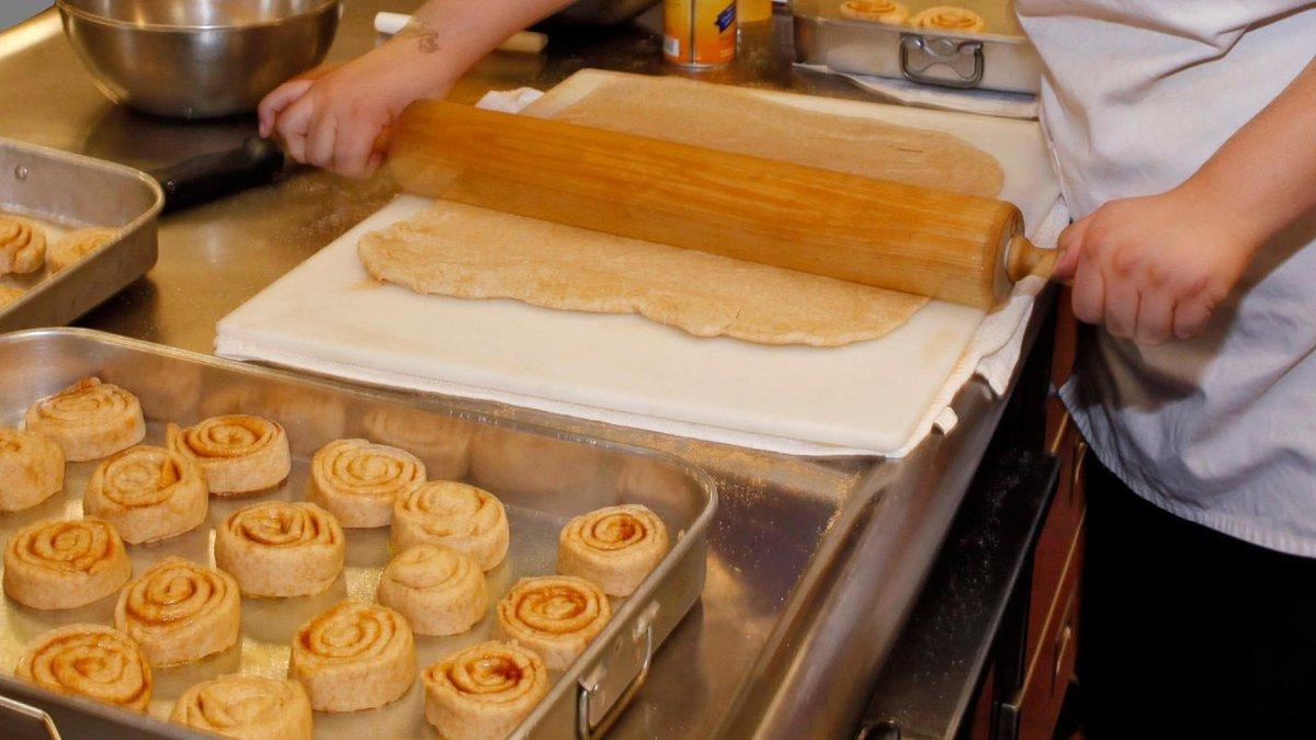 Baker rolling dough next to cinnamon rolls
