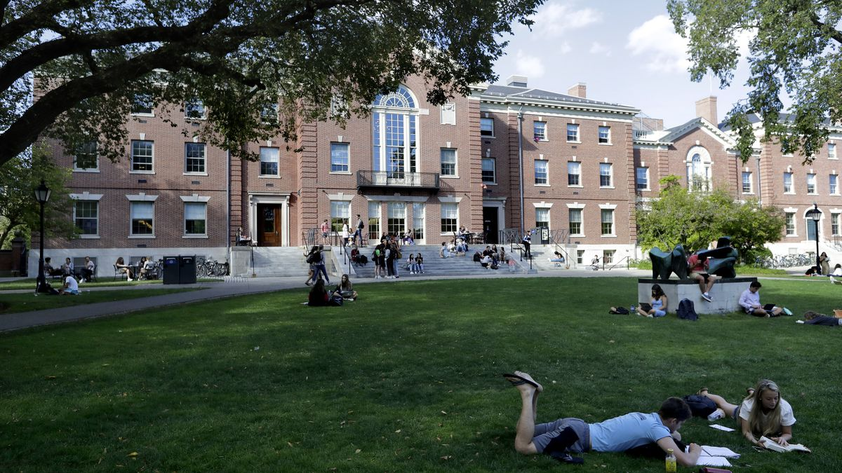In this Wednesday, Sept. 25, 2019 photo, people rest on grass while reading at Brown University, in Providence, R.I.