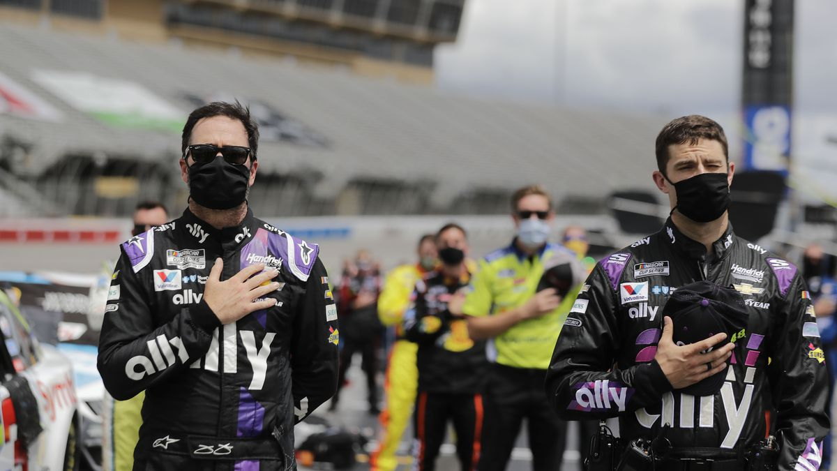Jimmie Johnson, left, and crew members stand in pit row during the national anthem before a NASCAR Cup Series auto race at Atlanta Motor Speedway, Sunday, June 7, 2020, in Hampton, Ga. (AP Photo/Brynn Anderson)