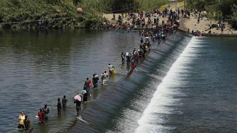 FILE - In this Sept. 18, 2021, file photo Haitian migrants use a dam to cross into the United...