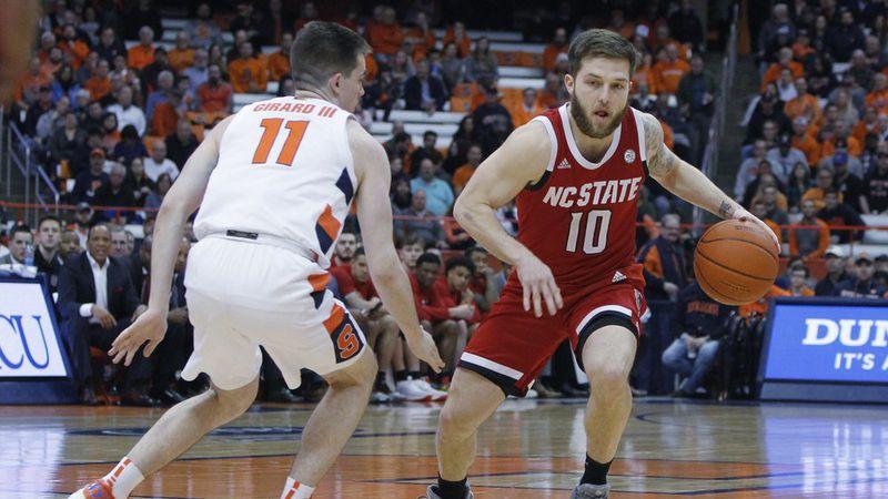 North Carolina State's Braxton Beverly, right, tries to dribble past Syracuse's Joseph Girard...