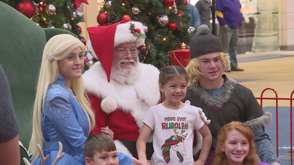 Santa Clause poses with a photo with a family | KALB