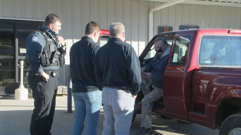 Edmonson County Sheriff Shane Doyle and local business owner Jeff Jacobs hand out $100 bills...