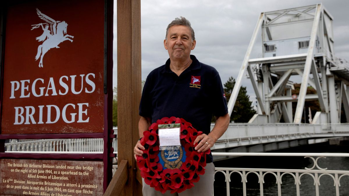 In this photo taken on Friday, June 5, 2020, British expatriate Steven Oldrid holds a poppy wreath as he stands on the site of the original WWII Pegasus Bridge in Benouville, Normandy, France. Due to coronavirus measures many relatives and veterans will not make this years 76th anniversary of D-Day. Oldrid will be bringing it to them virtually as he places wreaths and crosses for families and posts the moments on his facebook page. (AP Photo/Virginia Mayo)