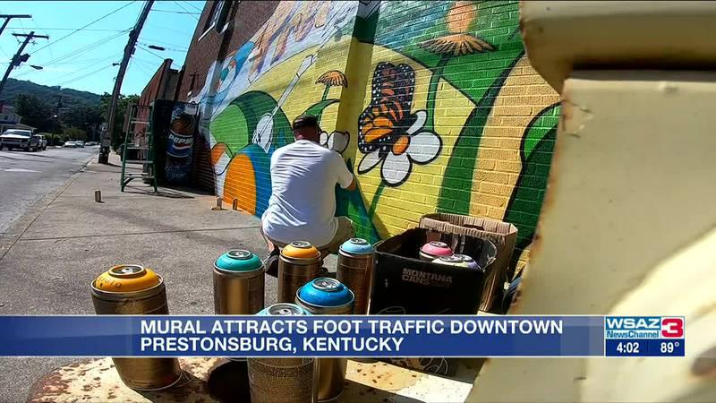 Casey McKinney, a Kentucky artist, paints a mural in downtown Prestonsburg.