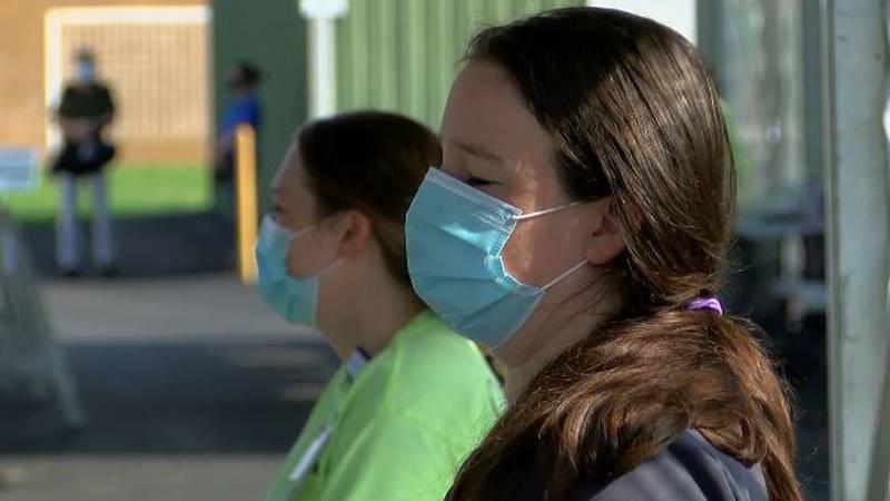 Two women wear masks outside of a store.