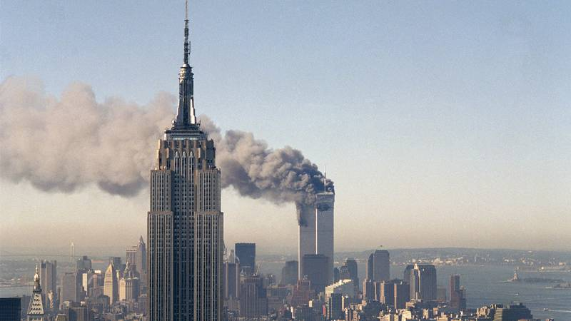 The twin towers of the World Trade Center burn behind the Empire State Building in New York,...