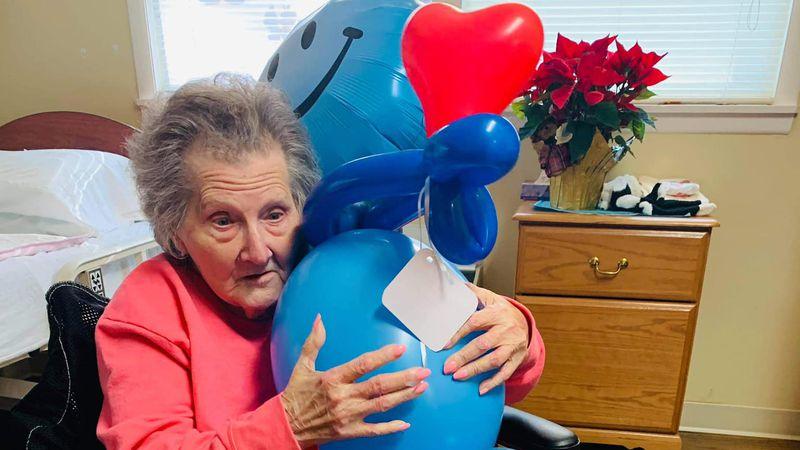 "Senior citizen poses with her ""balloon buddy."""