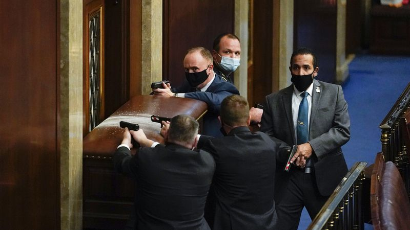 U.S. Capitol Police with guns drawn stand near a barricaded door as protesters try to break...