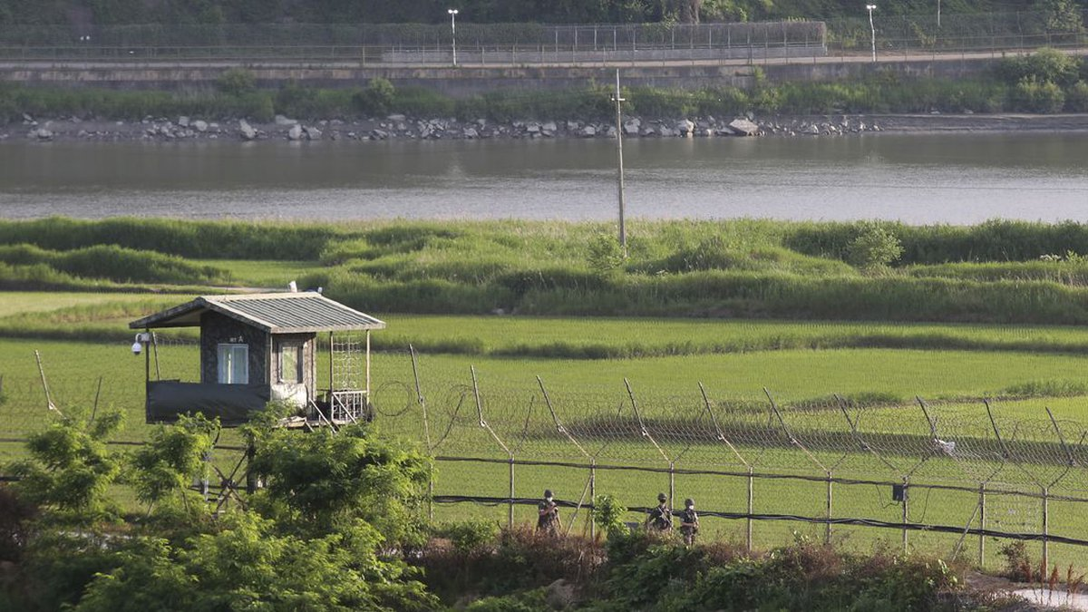 South Korean army soldiers patrol along the barbed-wire fence in Paju, South Korea, near the...