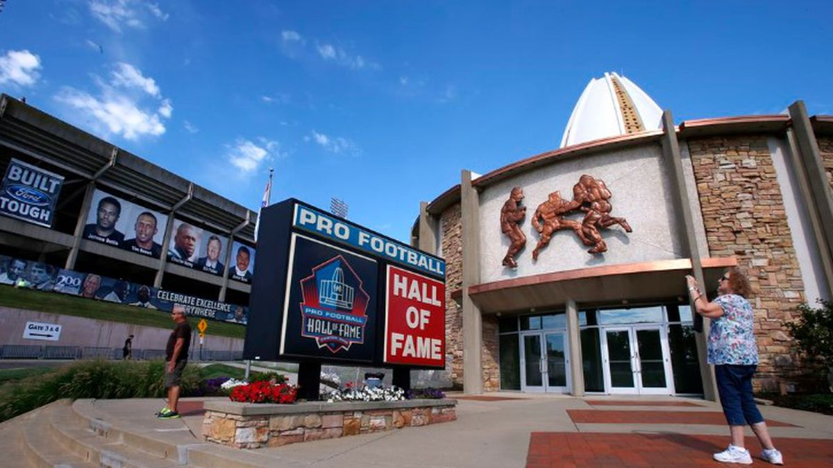 FILE - In this Aug. 7, 2015, file photo, a visitor to the Pro Football Hall of Fame pauses to take a photo of the sign in front in Canton, Ohio. The NFL has canceled the Hall of Fame game that traditionally opens the preseason and is delaying the 2020 induction ceremonies because of the coronavirus pandemic, two people with direct knowledge of the decision told The Associated Press on Thursday, June 25, 2020. The people spoke to the AP on condition of anonymity because the decision has not been publicly announced, though an announcement is expected later Thursday. (Source: AP Photo/Gene J. Puskar, File)
