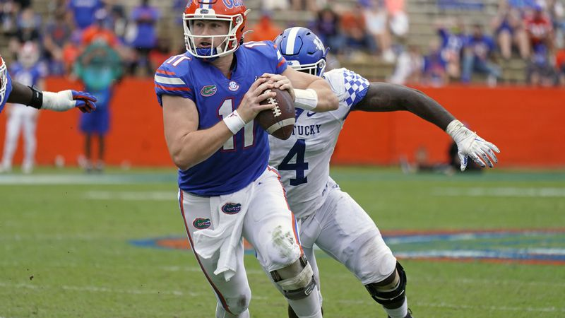 Florida quarterback Kyle Trask, left, scrambles away from Kentucky defensive end Joshua Paschal...